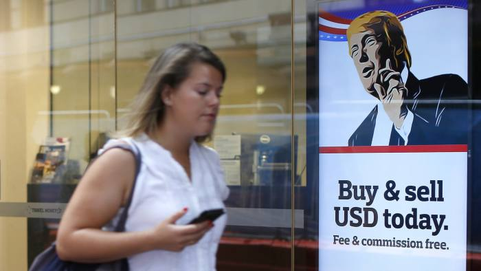A woman walks past an advertisement featuring a cartoon of U.S. President-elect Donald Trump at a currency exchange store in the central business district in Sydney, Australia, on Thursday, Nov. 10, 2016. Stocks in Asia rebounded from their steepest slide since Brexit, industrial metals surged and regional bonds tumbled after Trump's election victory and spending pledges spurred gains in U.S. shares. Photographer: David Moir/Bloomberg
