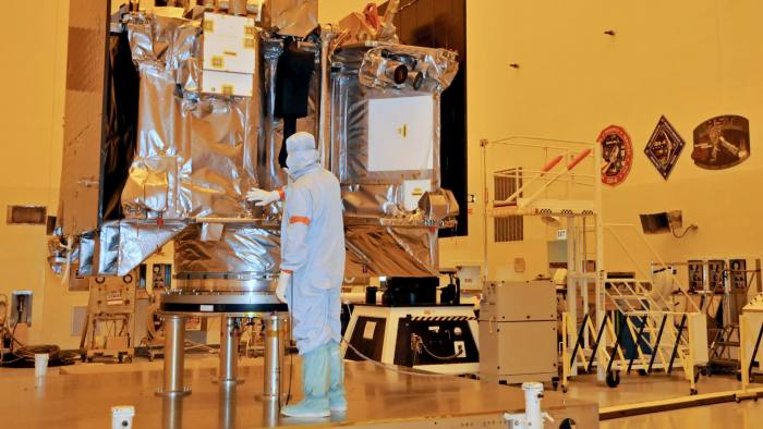 The OSIRIS-REx spacecraft sits on its workstand August 20, 2016 while an engineer checks the protective covering in a servicing building atKennedy Space Center, Florida. The OSIRIS-REx is scheduled to launch aboard an Atlas 5 rocket September 8, 2016 on its mission to the asteroid Bennu. / AFP / AFP PHOTO / Bruce Weaver (Photo credit should read BRUCE WEAVER/AFP/Getty Images)
