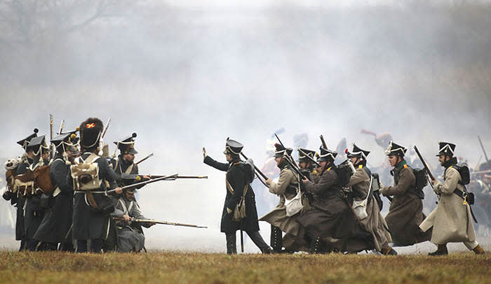 Men dressed as 1812-era Russian and French soldiers re-enact a staged battle near the Belarus village of Bryli, about 115 kilometers (70 miles) east of the capital, Minsk, Sunday, Nov. 26, 2017, to mark the 205th anniversary of the Berezina battle during Napoleon's army retreat from Russia. The retreat across the Berezina of the remnants of Napoleon's Grand Army, which invaded Russia June 24, 1812, took place from Nov. 26 to Nov. 29, 1812. (AP Photo/Sergei Grits)