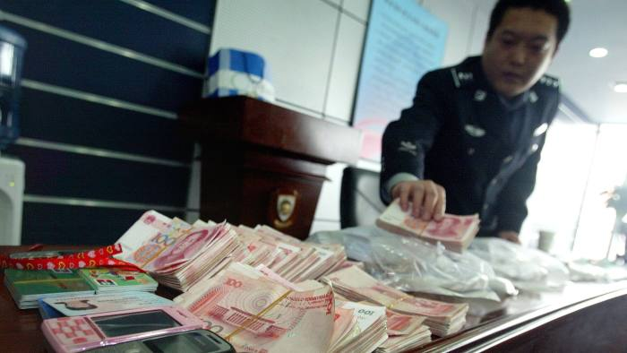 A Chinese policeman shows off cash and other seized items after a crackdown on a Taiwanese money laundering syndicate, during a press conference in Beijing on March 26, 2009. Experts fear the export-dependent Chinese economy slowing to 6.8 percent growth in the final quarter of 2008, and rising unemployment figures could cause a crime wave as China's 1.3 billion people struggle with the consequences of the global meltdown. CHINA OUT GETTY OUT AFP PHOTO / AFP / AFP