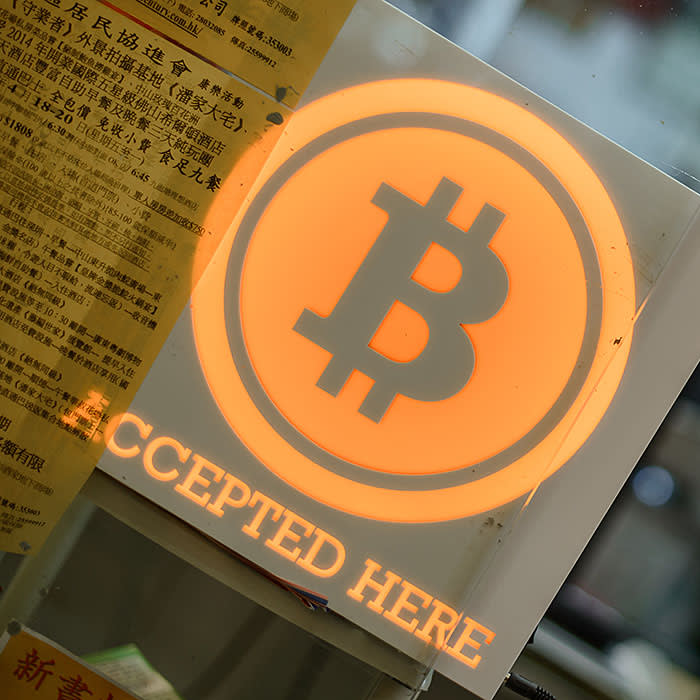 A man talks on a mobile phone in a shop displaying a bitcoin sign during the opening ceremony of the first bitcoin retail shop in Hong Kong on February 28, 2014. Bitcoin was invented in the wake of the global financial crisis by a mysterious computer guru using the pseudonym Satoshi Nakamoto and unlike other currencies, it does not have the backing of a central bank or government. AFP PHOTO / Philippe Lopez / AFP PHOTO / PHILIPPE LOPEZ