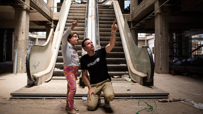 Mirna, aged 11, shows Ewan McGregor the abandoned, half-finished shopping mall, where she lives with her family in Erbil, Iraq