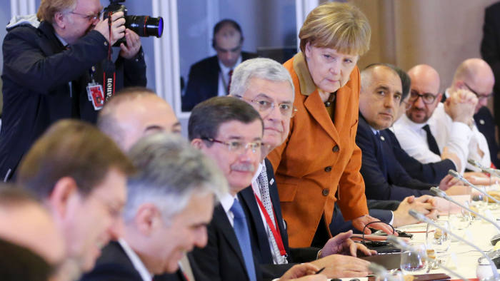 Turkish Prime Minister Ahmet Davutoglu (4th L), German Chancellor Angela Merkel (4th R) and other European leaders attend the lunch of a European Union leaders' summit with Turkey on the migrant crisis at the European Council in Brussels, on March 7, 2016. EU leaders held a summit with Turkey's prime minister on March 7 in order to back closing the Balkans migrant route and urge Ankara to accept deportations of large numbers of economic migrants from overstretched Greece. The European Union is hardening its stance in a bid to defuse the worst refugee crisis since World War II by increasingly putting the onus on Turkey and EU member Greece in return for aid. / AFP / POOL / OLIVIER HOSLETOLIVIER HOSLET/AFP/Getty Images