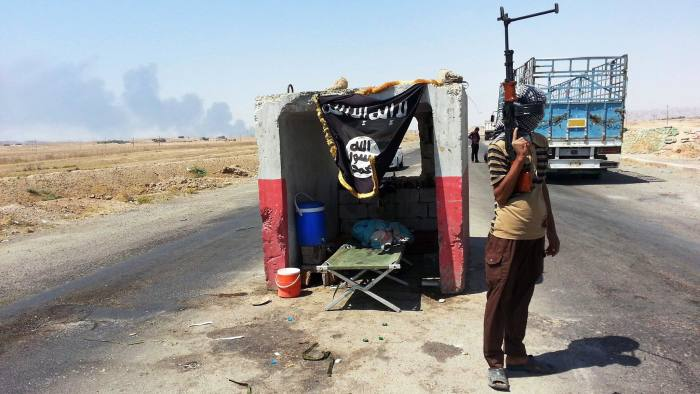 An al-Qaida-inspired militant stand guard at a checkpoint captured from the Iraqi Army outside Beiji refinery, some 250 kilometers (155 miles) north of Baghdad, Iraq, Thursday, June 19, 2014. The fighting at Beiji comes as Iraq has asked the U.S. for airstrikes targeting the militants from the Islamic State of Iraq and the Levant. While U.S. President Barack Obama has not fully ruled out the possibility of launching airstrikes, such action is not imminent in part because intelligence agencies have been unable to identify clear targets on the ground, officials said.(AP Photo)(AP Photo)