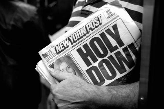 A person holding a New York Post newspaper headlined with news of the Dow Jones drop on 2008