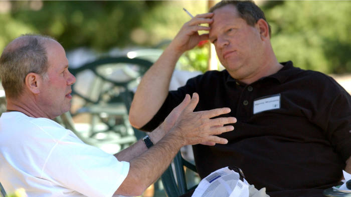 Walt Disney Co. CEO Michael D. Eisner, left, talks with Miramax Film Corp. Co-Chairman Harvey Weinstein on the grounds of the Sun Vally resort during the Allen & CO conference in Sun Valley, Idaho, Thursday, July 8, 2004. Photographer: Matthew Staver/Bloomberg News.