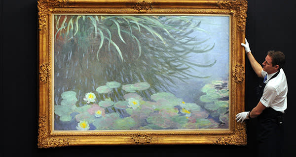 A member of staff poses with a painting entitled 'Nympheas avec reflets de hautes herbes' by French artist Claude Monet at Sotheby's auction house in central London on January 31, 2013. Due to form part of the Impressionist and Modern Art Evening Sale on February 5, it is expected to fetch between 12-18 million GBP (15-22 million EUR - 19-29 million USD). AFP PHOTO / CARL COURT (Photo credit should read CARL COURT/AFP/Getty Images)