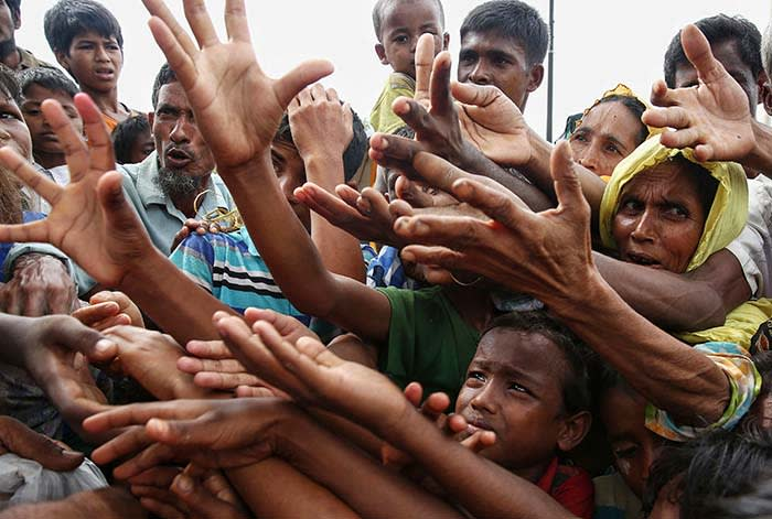 TOPSHOT - This August 30, 2017 photo shows Rohingya refugees reaching for food aid at Kutupalong refugee camp in Ukhiya near the Bangladesh-Myanmar border. The International Organization for Migration said August 30 that at least 18,500 Rohingya had crossed into Bangladesh since fighting erupted in Myanmar's neighbouring Rakhine state six days earlier. / AFP PHOTO / STRSTR/AFP/Getty Images