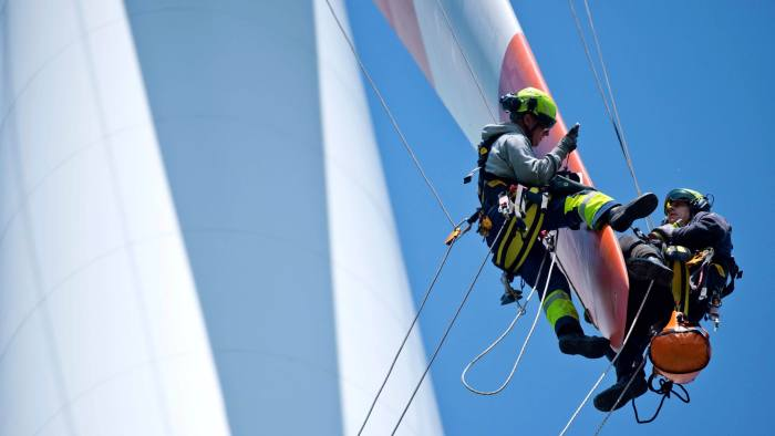 In this picture made available Friday May 17, 2013, two maintenance workers control the rotor blades of a wind turbine near Sieversdorf, Germany Thursday May 16, 2013.   (AP Photo/dpa,Patrick Pleul)