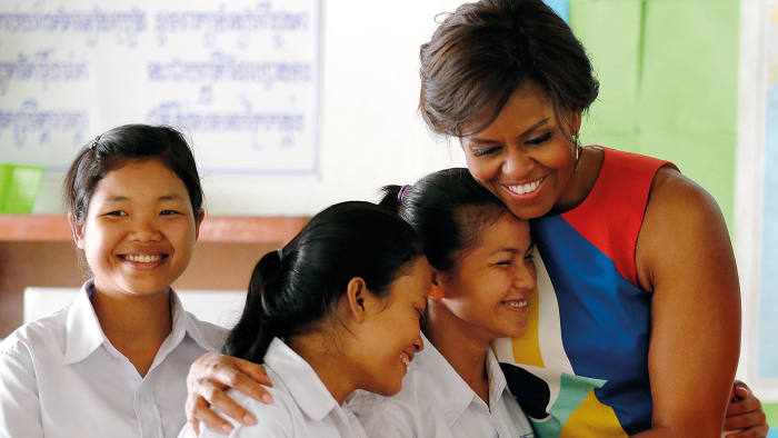 "US first lady Michelle Obama, center, hugs students at a local high school that she visited with Bun Rany, the first lady of Cambodia, second right, Saturday, March 21, 2015, on the outskirts of Siem Reap, Cambodia. Mrs. Obama is in Cambodia to promote the education initiative ""Let Girls Learn,"" which was launched to lift barriers that block more than 62 million girls around the world from attending school. (AP Photo/Wong Maye-E)"