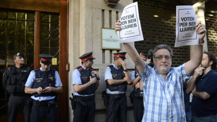 """A man hols pro-referendum posters reading in Catalan """"Vote to be free"""" as Spanish Civil Guards and Catalan regional police officers 'Mossos D'Esquadra"""" stand in front of the Economy headquarters of Catalonia's regional government in Barcelona on September 20, 2019, during a search by Spain's Guardia Civil police. The operation comes amid mounting tensions as Catalan leaders press ahead with preparations for an independence referendum on October 1 despite Madrid's ban and a court ruling deeming it illegal. / AFP PHOTO / Josep LAGOJOSEP LAGO/AFP/Getty Images"""