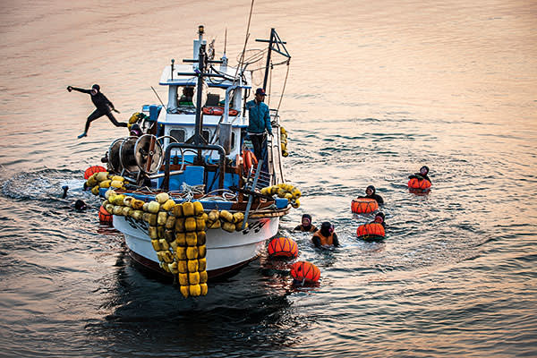 A diver jumps from a fishing boat off Jeju as other haenyeo clutch the orange buoys to which they attach their seaweed sacks