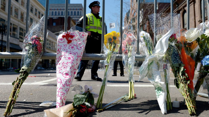Flowers are seen along a police barricade down the street from the finish line of the Boston Marathon as an investigation continues into dual bombings at the site