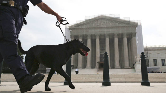 A police officer walks his dog in front of the U.S. Supreme Court building June 17, 2013