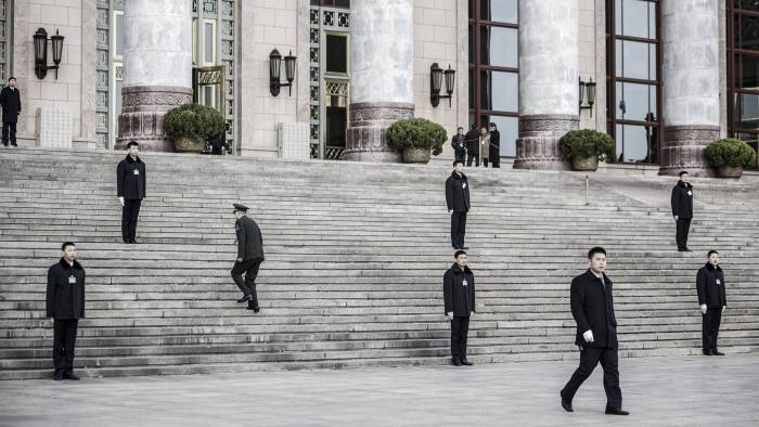 Bloomberg Best of the Year 2017: A delegate walks up a flight of stairs as attendants stand outside the the Great Hall of the People ahead of the opening of the fifth session of the 12th National People's Congress (NPC) in Beijing, China, on Sunday, March 5, 2017. Photographer: Qilai Shen/Bloomberg