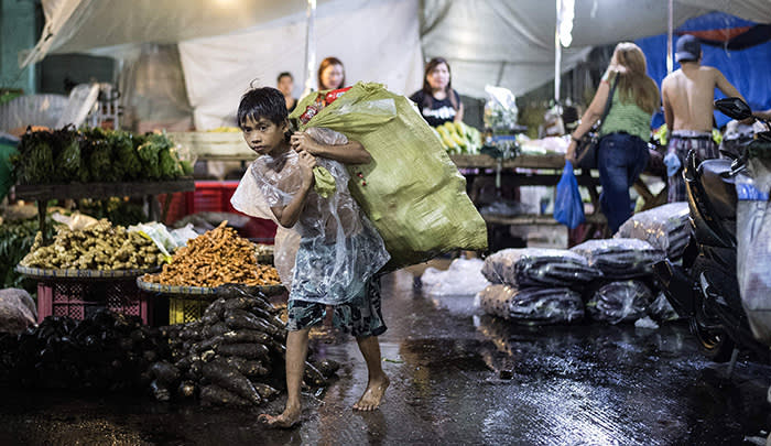 TOPSHOT - A Philippine boy collects used plastic bottles to be sold at a junk shop at Divisoria market in Manila on November 29, 2017. / AFP PHOTO / NOEL CELISNOEL CELIS/AFP/Getty Images