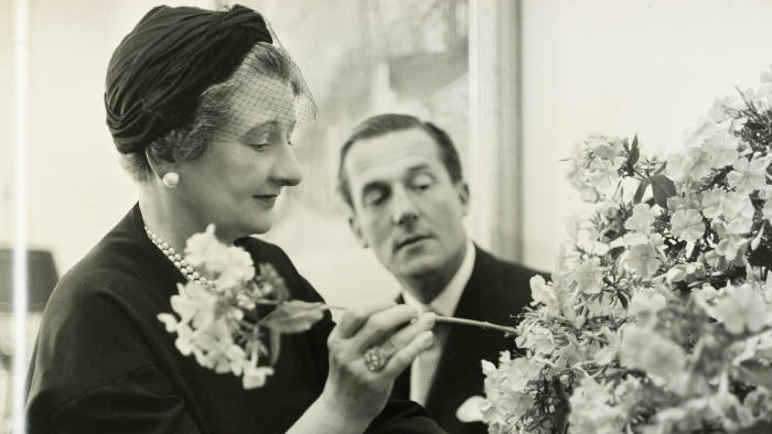 Constance Spry, arranging white flowers, with fashion designer Hardy Amies in 1960