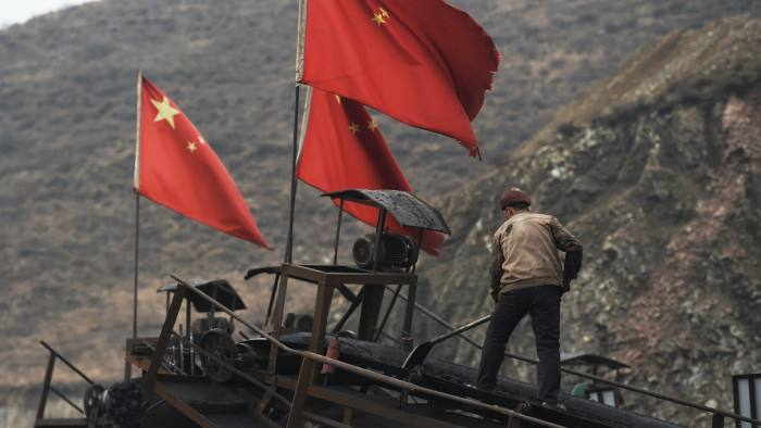 TO GO WITH China-economy-environment-coal-climate,FOCUS by Tom HANCOCK In this photo taken on November 20, 2015, Chinese flags fly as a worker clearing a conveyer belt used to transport coal, near a coal mine at Datong, in China's northern Shanxi province. For decades coal has been the backbone of the northern province of Shanxi, providing livelihoods for millions of miners, while private jet owning bosses became notorious for their nouveau riche lifestyles. AFP PHOTO / GREG BAKER / AFP / GREG BAKER (Photo credit should read GREG BAKER/AFP/Getty Images)