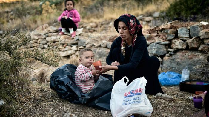 A woman feeds a baby near the overcrowded hotspot on the Greek eastern Aegean islands of Samos on October 13, 2017. More than 3,000 people on Samos are crammed into facilities designed to hold 700. Some 200 people, including families with children, are sleeping in tents in the woods due to a lack of space in the camp. Nearly 5,000 refugees, mostly Syrian or Iraqi families, crossed from Turkey to Greece in September - a quarter of all arrivals this year, UNHCR data shows. / AFP PHOTO / LOUISA GOULIAMAKILOUISA GOULIAMAKI/AFP/Getty Images