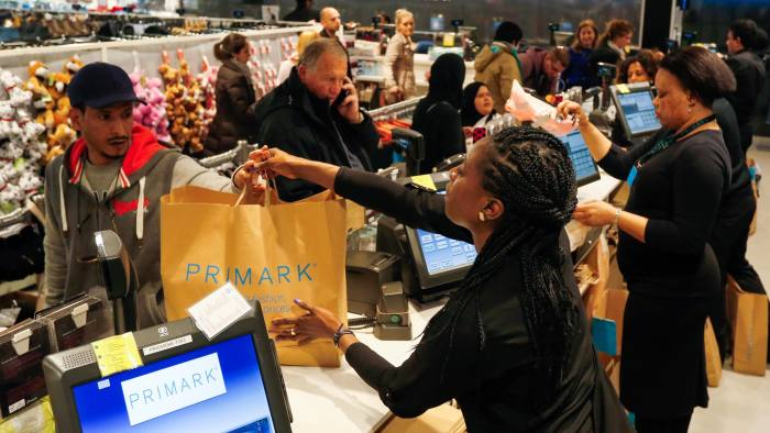 A cashier hands shopping to a customer at a Primark clothing store, operated by Associated British Foods Plc, on Oxford Street in London, U.K., on Friday, Feb. 26, 2016. Diversification has helped power Primark from its birth in the 1960s as an Irish discount clothing chain to aggressive expansion across Europe and more recently into the U.S. Photographer: Luke MacGregor/Bloomberg