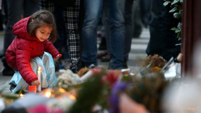 A young girl leaves a lit candle outside Le Carillon bar, Paris, one of the venues for the attacks in the French capital which are feared to have killed around 127 people. PRESS ASSOCIATION Photo. Issue date: Saturday November 14, 2015. A state of emergency has been declared in France after a night of horror in the capital. There were two suicide attacks and a bombing near the Stade de France stadium, shootings at restaurants and a massacre inside a popular music venue in what is the worst violence to hit France since the Second World War. See PA story POLICE Paris. Photo credit should read: Steve Parsons/PA Wire