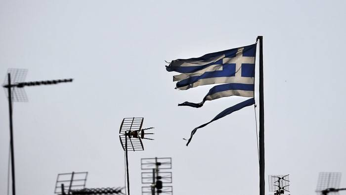 File photo shows a frayed Greek national flag fluttering among antennas atop a building in central Athens...A frayed Greek national flag flutters among antennas atop a building in central Athens, Greece in this file photo taken July 20, 2015. To match Exclusive EUROZONE-GREECE/DEBT REUTERS/Alkis Konstantinidis/Files