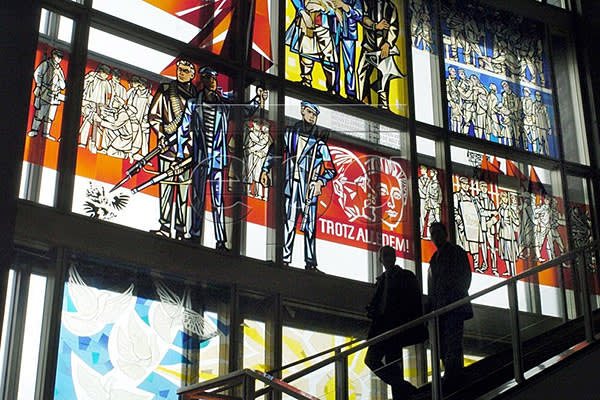 Two people walk past a window pane with images which is under monumental protection, inside the former GDR State Council building in Berlin