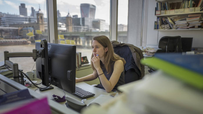 "FT reporter, Sarah O'Connor, studies the UK employment figures ahead of writing an article for the Financial Times in competition with the algorithm ""Emma""."