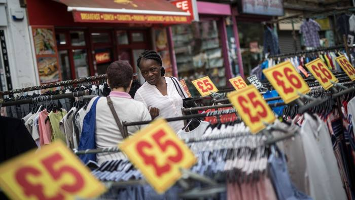Customers browse cloths as signs advertise pound sterling prices above clothing rails on a stall on a stall in Petticoat Lane market in London, U.K., on Friday, July 14, 2017. The U.K. acknowledged for the first time in writing that it will have to pay money to the European Union when it withdraws from the bloc, seeking to damp down a row over the countrys so-called Brexit bill. Photographer: Simon Dawson/Bloomberg