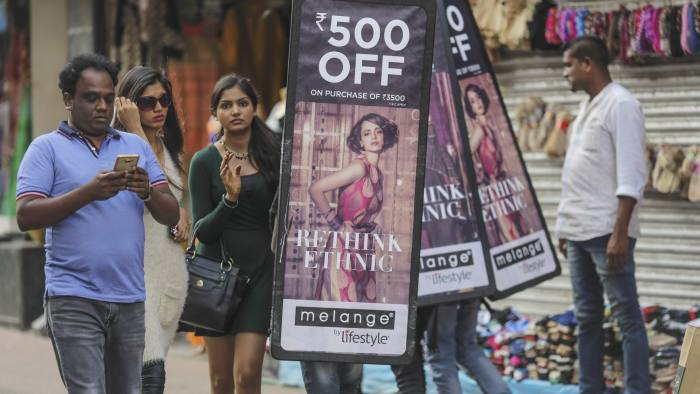 Pedestrians holding walks past people carrying advertisements for a local clothing store in Bangalore, India