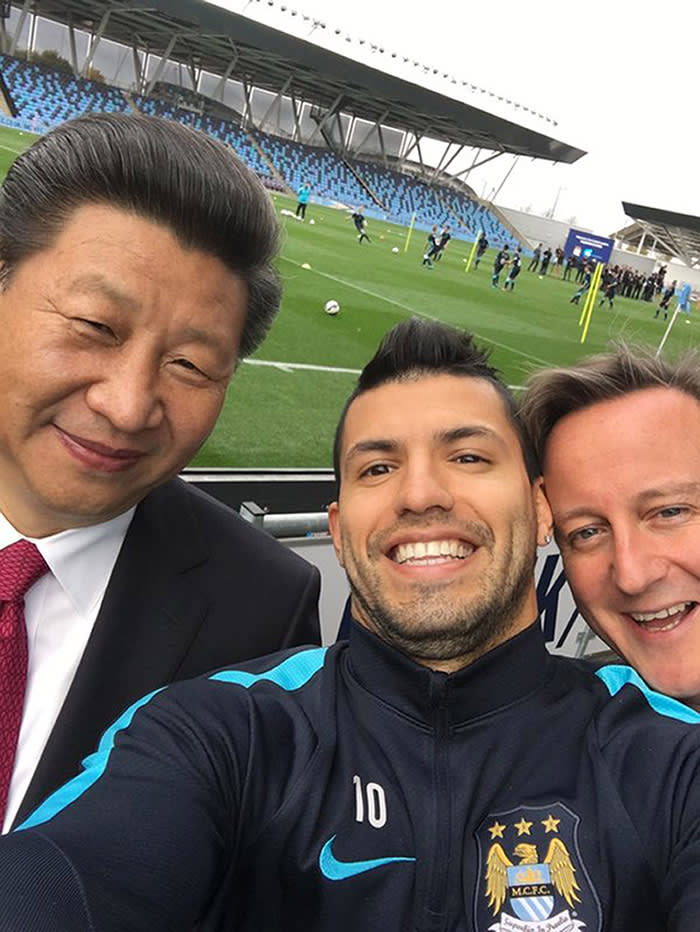 In this handout photo issued by Manchester City Football Club, soccer player Sergio Aguero takes a selfie with Britain's Prime Minister David Cameron, right, and Chinese President Xi Jinping, during a visit on the fourth day of his state visit, in Manchester, England, Friday Oct. 23, 2015. Chinese President Xi Jinping has been greeted by hundreds of enthusiastic and well-organized well-wishers in the northwest England city of Manchester. Crowds waving Chinese flags have greeted Xi throughout his four-day state visit to Britain, outnumbering pro-Tibet and human rights protesters concerned about the British government's lavish welcome for the Chinese leader. (Photo/Sergio Aguero, Manchester City Fooball Club via AP)