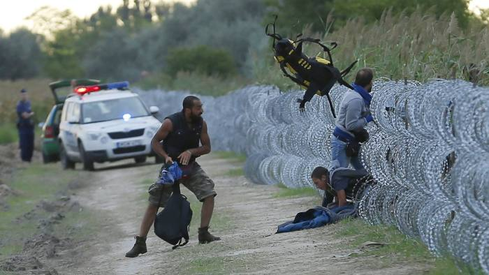 Hungarian police positioned nearby watch as Syrian migrants climb under a fence to enter Hungary at the Hungarian-Serbian border near Roszke, Hungary August 26, 2015. Hungary's government has started to construct a 175-km-long (110-mile-long) fence on its border with Serbia in order to halt a massive flow of migrants who enter the EU via Hungary and head to western Europe. REUTERS/Laszlo Balogh TPX IMAGES OF THE DAY