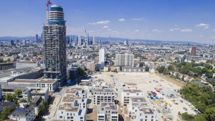 Apartment blocks sit on a building site beside the under construction Henninger Tower, a residential and a retail property development by Actris GmbH, as skyscrapers stand on the city skyline beyond in Frankfurt, Germany, on Tuesday, July 19, 2016. A U.K. exit from the European Union will boost commercial real-estate prices in Frankfurt, accelerating a trend that has already pushed building values to record highs, according to CA Immobilien Anlagen AG. Photographer: Martin Leissl/Bloomberg