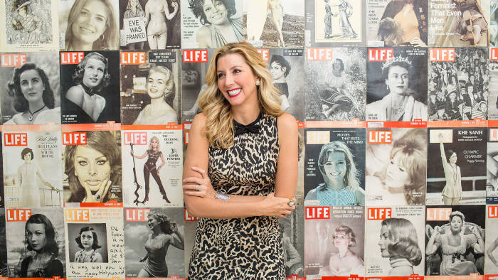 Spanx founder Sara Blakely poses for a portrait in her office against a wall of LIFE magazine covers