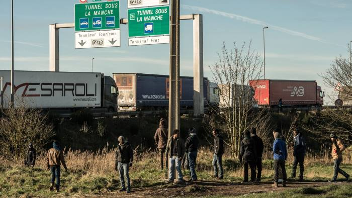 "Migrants stand near the A16 motorway near the site of the Eurotunnel in Coquelles, near Calais, northern France on January 21, 2016. Approximately 300 migrants have tried to board trucks protected by French police, according to an estimate made by an AFP photographer present at the scene. Clashes already erupted briefly on the night of January 20 at the port bypass Calais between several hundred migrants and security forces, who fired tear gas to restore the situation, according to an AFP correspondent. These incidents occurred after the prefecture of Pas-de-Calais had set an ultimatum which expired early in the afternoon for the last migrants to leave a deforested 100 metre strip of the ""Jungle"" camp along the ring road for safety reasons. / AFP / PHILIPPE HUGUEN (Photo credit should read PHILIPPE HUGUEN/AFP/Getty Images)"