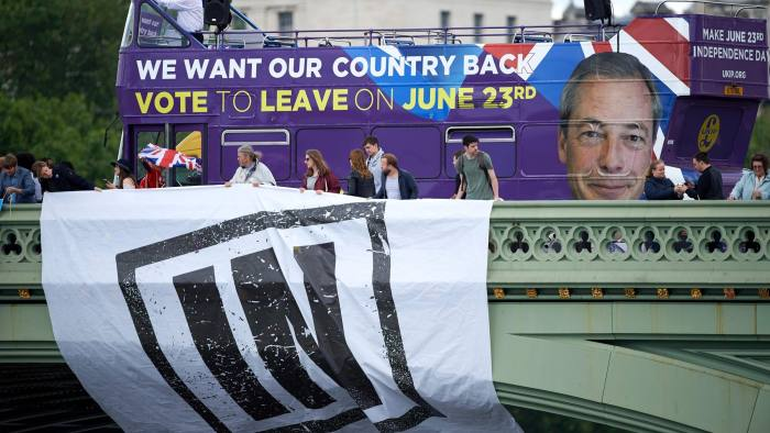 Campaigners to remain in the EU unfurl a banner on Westminster Bridge as a bus bearing the face of UKIP leader Nigel Farage and a message urging voters to leave the EU in the upcoming referendum sits behind it as they wait for a flotilla of boats from the group 'Fishing for Leave' to sail by on the river Thames in London on June 15, 2016. A Brexit flotilla of fishing boats sailed up the River Thames into London today with foghorns sounding, in a protest against EU fishing quotas by the campaign for Britain to leave the European Union. / AFP PHOTO / NIKLAS HALLE'NNIKLAS HALLE'N/AFP/Getty Images