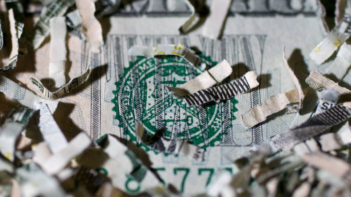 Shredded currency surrounds the seal of the US Treasury on a twenty dollar bill in Washington, DC, US, on Wednesday, April 24 2013.