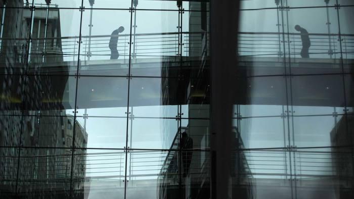 A worker crosses a city of London walkway