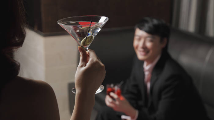Rear view of young woman holding a drink looking at a man