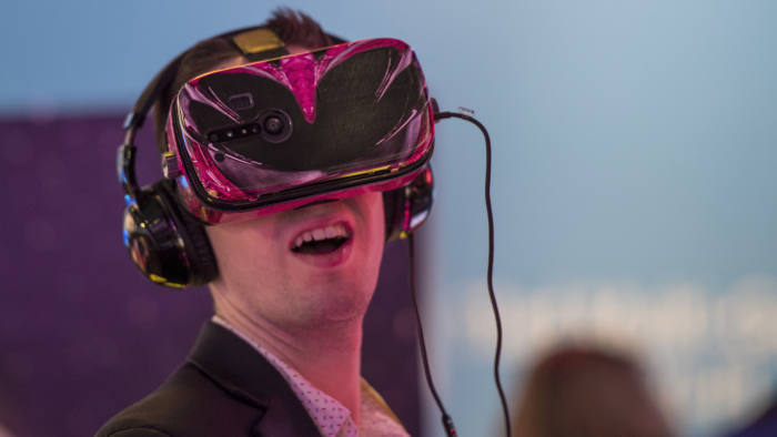 An attendee experiences a virtual reality (VR) headset powered by a Qualcomm Inc. Snapdragon 835 processor at the 2017 Consumer Electronics Show (CES) in Las Vegas, Nevada, U.S., on Friday, Jan. 6, 2017. CES, celebrating its 50th year, will showcase self-driving cars, TVs, drones, robots and a slew of other gadgets. Photographer: David Paul Morris/Bloomberg