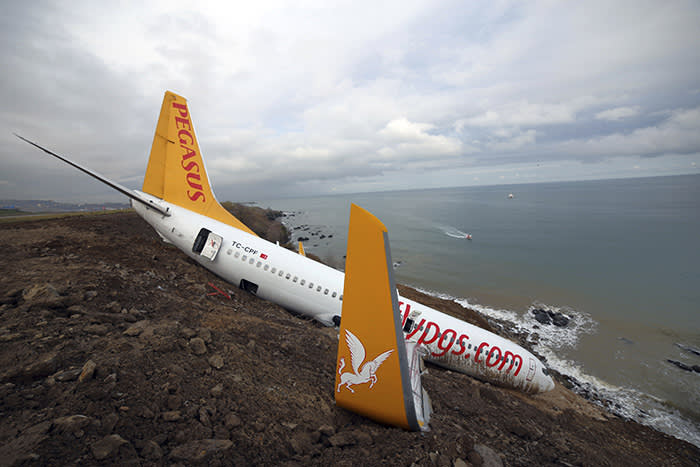"""A Boeing 737-800 of Turkey's Pegasus Airlines is seen in Trabzon, Turkey, Monday, Jan. 15, 2018. A commercial airplane that skidded off a runway after landing in northern Turkey dangled precariously Sunday off a muddy cliff with its nose only a few feet from the Black Sea.Some of the 168 people on board the Boeing 737-800 described it as a """"miracle"""" that everyone was evacuated safely from the plane, which went off a runway at Trabzon Airport. (DHA-Depo Photos via AP)"""