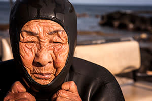Ra Wal-soo, 89, donning her wetsuit as she gets ready to dive