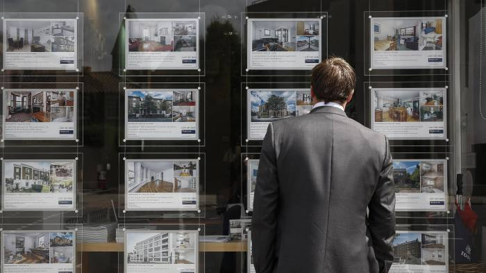 A pedestrian reads property information leaflets displayed in the window of Winkworth's estate agent's in the Kennington district of London, U.K., on Monday, Aug. 18, 2014. London home sellers cut asking prices by the most in more than six years this month, adding to signs that the property market in the U.K. capital is coming off the boil. Photographer: Simon Dawson/Bloomberg