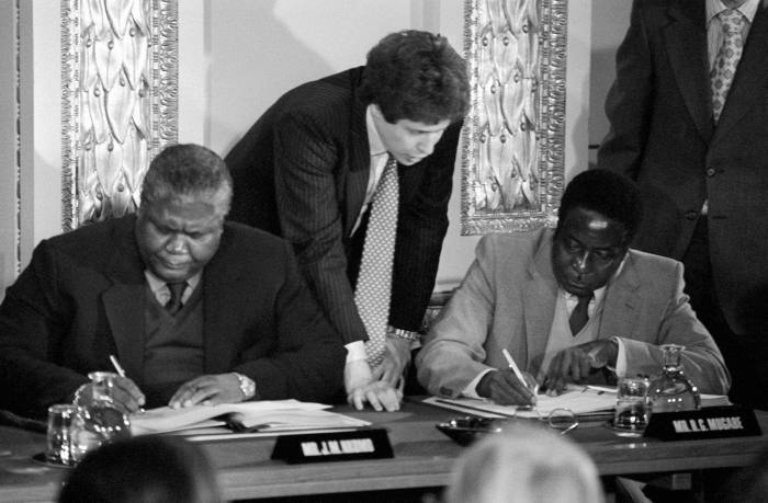 Guerrilla leaders Joshua Nkomo (L) and Robert Mugabe (R) signing the Rhodesia ceasefire agreement for the Patriotic Front at Lancaster House in London.