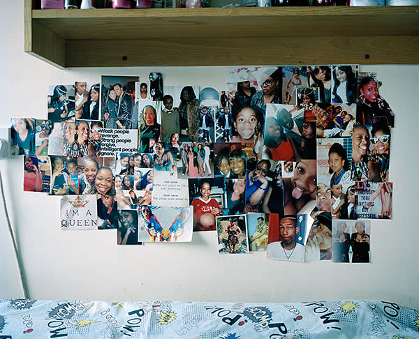 Photographs of friends and family above the bed