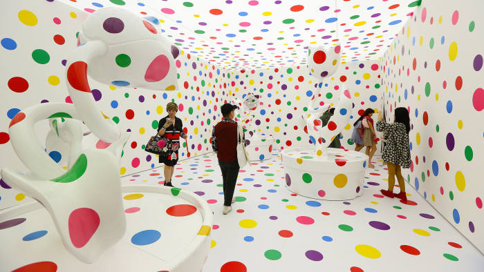 SINGAPORE - JUNE 06: Visitors stand inside Japanese artist, Yayoi Kusama metal, fibreglass, urethane, paint, stickers installation titled 'With All My Love for Tulips, I Pray Forever 2013' during a media preview at National Gallery Singapore on June 6, 2017 in Singapore. Yayoi Kusama: Life is the Heart of a Rainbow exhibition features over 120 works spanning 70 years of Kusama's artistic practise. The exhibition runs from June 9 to September 3, 2017. (Photo by Suhaimi Abdullah/Getty Images)