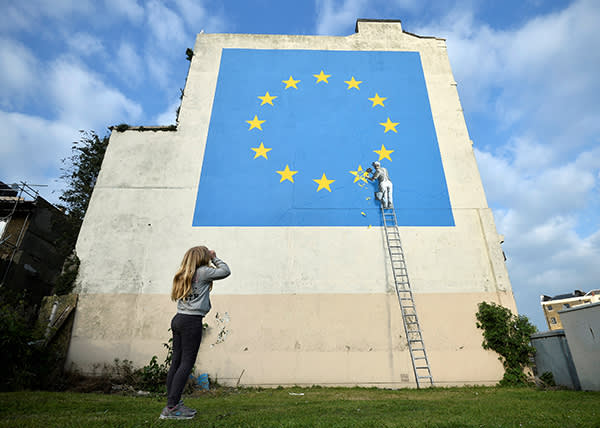 A young girl looks at artwork attributed to street artist Banksy, depicting a workman chipping away at one of the 12 stars on the European Union, seen on a wall in the ferry port of Dover, Britain, May 7, 2017. REUTERS/Hannah McKay FOR EDITORIAL USE ONLY. NO RESALES. NO ARCHIVES. TPX IMAGES OF THE DAY