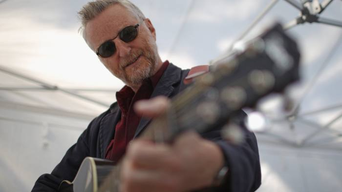MANCHESTER, ENGLAND - OCTOBER 04: Billy Bragg waits to perform before the start of an anti-austerity protest during the first day of the Conservative Party Autumn Conference 2015 on October 4, 2015 in Manchester, England. Up to 80,000 people are expected to attend a demonstration today organised by the TUC and anti-austerity protesters. Conservative Party members are in Manchester for its first conference as a party in a majority government since 1996. (Photo by Christopher Furlong/Getty Images)