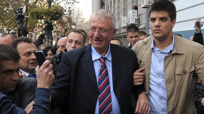 Serbian nationalist Vojislav Seselj supported by his son Aleksandar arrives at the Radical party headquarters in Zemun near Belgrade on November 11, 2014. Seselj arrived after spending 12 years on trial at the Hague Criminal Tribunal for the former Yugoslavia. Seselj, whose alleged atrocities, defiant rhetoric and taunting of war crimes judges made him a symbol of the 1990s Balkan conflicts, has been temporally released by the ICTY because of medical treatment. AFP PHOTO / ALEXA STANKOVIC (Photo credit should read ALEXA STANKOVIC/AFP/Getty Images)