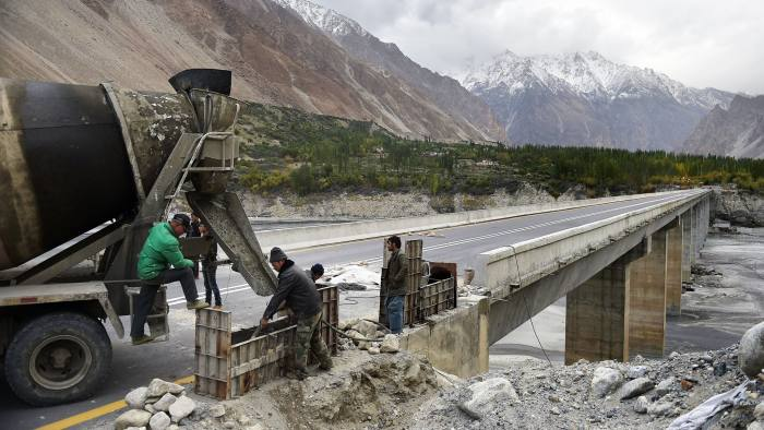 To go with story 'Pakistan-China-economy-transport, FEATURE' by Guillaume LAVALLÉE In this photograph taken on September 29, 2015, Chinese labourers work on the Karakoram highway in Gulmit village of Hunza valley in northern Pakistan. A glossy highway and hundreds of lorries transporting Chinese workers by the thousands: the new Silk Road is under construction in northern Pakistan, but locals living on the border are yet to be convinced they will receive more from it than dust. AFP PHOTO / Aamir QURESHI (Photo credit should read AAMIR QURESHI/AFP/Getty Images)